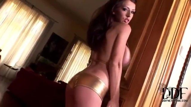 Sweetheart with large natural marangos teases and disrobes in shiny gold bikini and hotpants